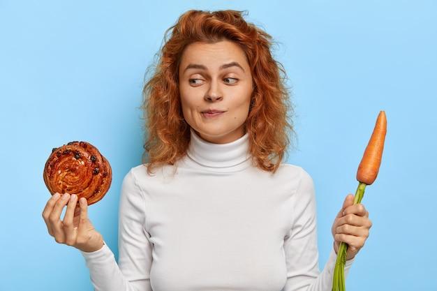 躊躇するセクシーな女の子は、ジャンクフードと新鮮な野菜に疑いを持ち、ダイエットを続け、焼きたてのおいしいロールとニンジンを保持し、誘惑を感じ、カジュアルな服を着て、屋内でモデル化します。栄養の概念