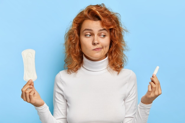 Hesitant ginger woman looks confusingly at sanitary napkin and tampon