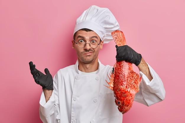 Chef maschio esitante vestito in uniforme e cappello, guanti neri, detiene il branzino rosso, non sa cosa cucinare, lavora al ristorante