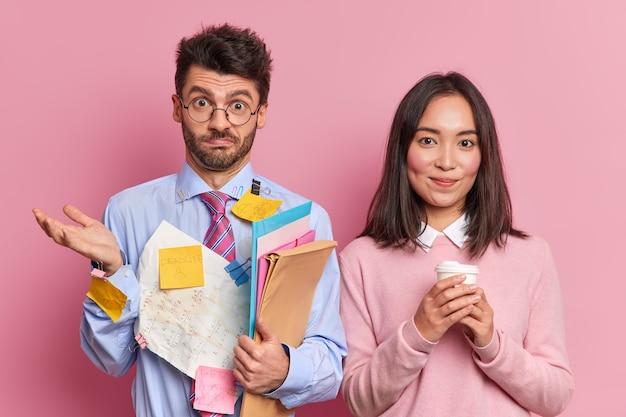 躊躇している男性起業家が肩をすくめる紙の文書を保持し、紙コップのコーヒーを保持している女性の同僚とビジネスプロジェクトの解決策について話し合います。パートナーシップと協力の概念