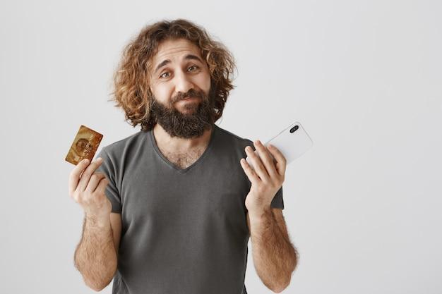 Esitante uomo mediorientale con carta di credito e cellulare, che scrolla le spalle all'oscuro