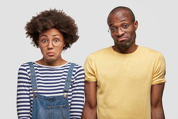 Нерешительно озадаченные темнокожие смешанные расы симпатичные женщина и мужчина в недоумении пожимают плечами