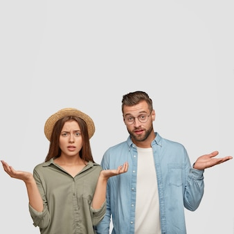 Hesitant puzzled indignant young caucasian woman and man shrug shoulders with uncertainty