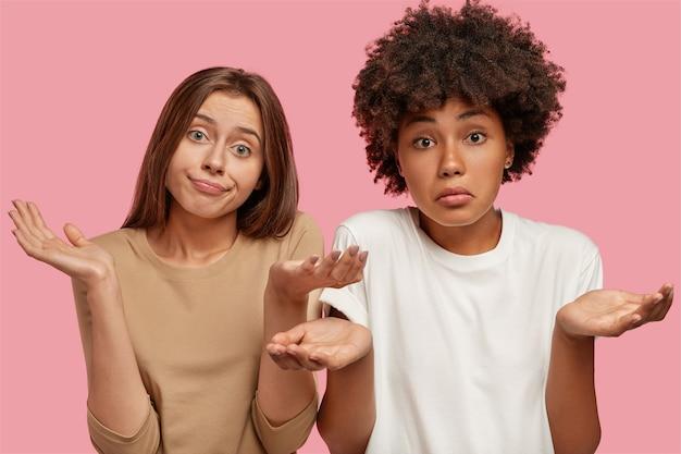 躊躇する混血の姉妹は不確実性で肩をすくめる