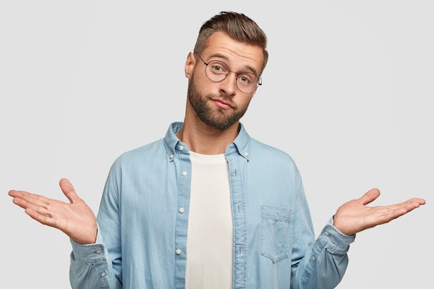 Hesitant puzzled unshaven man shruggs shoulders in bewilderment, feels indecisive, has bristle, trendy haircut, dressed in blue stylish shirt, isolated on white wall. clueless male poses indoor