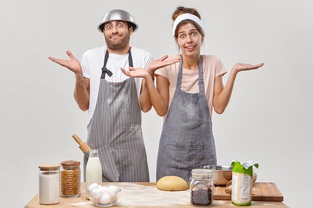 Esitante interrogato giovane donna e uomo alzano le spalle, stanno insieme in grembiule, non sanno cosa cucinare o quali ingredienti aggiungere, fanno l'impasto per la torta. i lavoratori del forno in cucina preparano una gustosa torta
