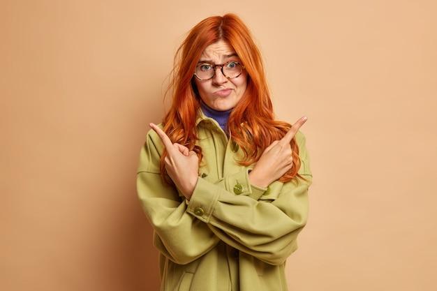 La giovane donna dai capelli rossi esitante indica di traverso mentre cerca di scegliere tra due opzioni sorride e rimane confusa