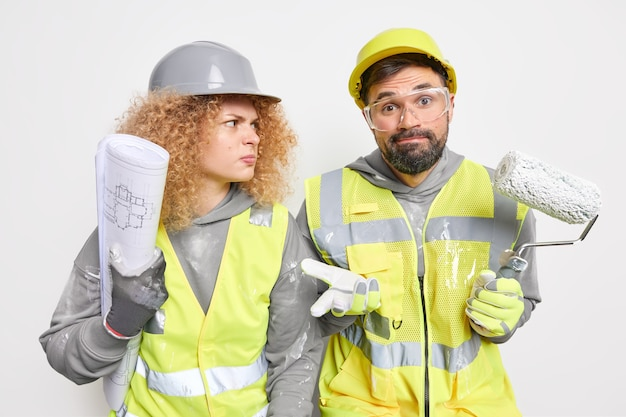 Hesitant repairman holds paint roller cannot decide something serious angry woman engineer wears hardhat and safety uniform holds blueprint. two professional builders pose on construction site