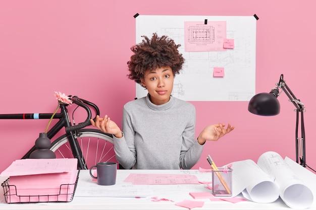 躊躇する才能のある女性建築家が手のひらを広げ、デスクトップで混乱したポーズをデザインスケッチを改善する方法を知らない