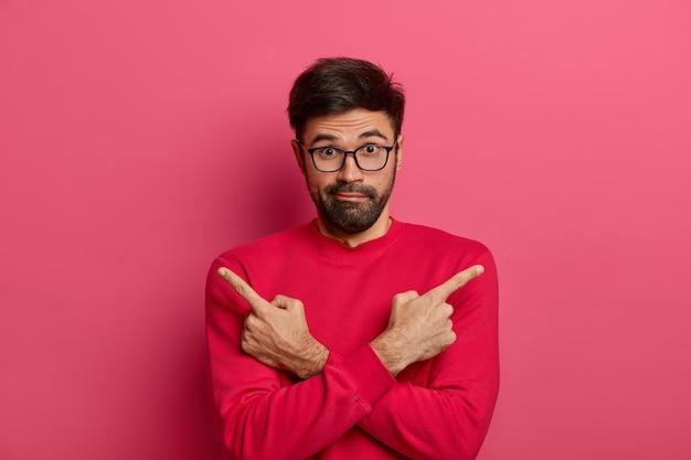 Un uomo con la barba lunga esitante incrocia le braccia sul corpo e indica di lato