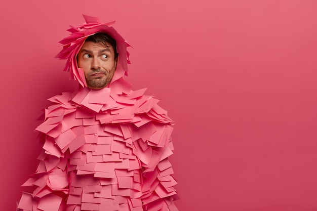 Hesitant unshaven young man looks aside, wears paper costume, uses office sticky notes, thinks about something, poses against pink wall, copy space for your advertisement or promotion.