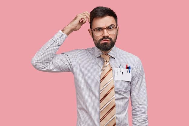 Неуверенный в себе мужчина-дизайнер чешет затылок и смотрит с серьезным выражением лица, думает о новых набросках, носит строгую рубашку, в кармане есть ручки и карандаш.