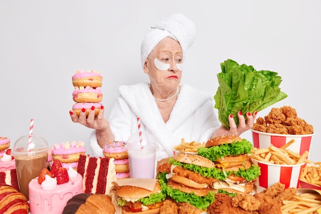 주저하는 여성 연금 수급자는 건강한 음식과 건강에 해로운 음식 사이에서 도넛과 녹색 채소를 가지고 있습니다.