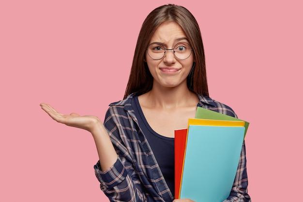 Esitante giovane imprenditrice in posa contro il muro rosa con gli occhiali