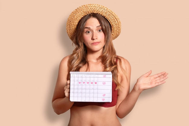 Hesitant young female has vacation abroad, holds period calendar, wonders why she has not regular menstruation, wears stylish straw hat, isolated over studio wall. women health concept.