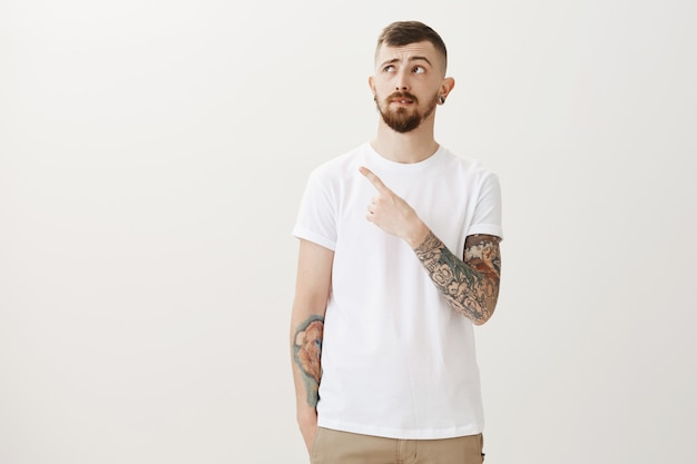 Hesitant young guy with tattoos pointing and looking upper left corner doubtful