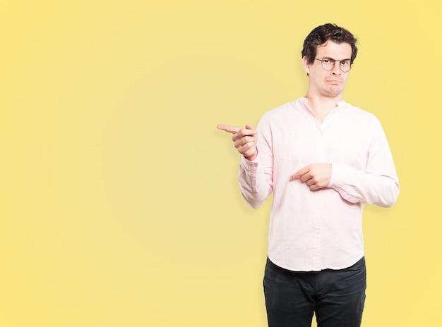 Сомневающийся молодой человек, указывая на вас пальцем