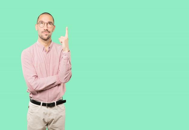 Сомневающийся молодой человек, указывая пальцем