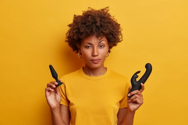 주저하는 아프리카 계 미국인 여성은 엉덩이 플러그를 잡고 침투 놀이를하기 전에 몸을 따뜻하게하고, 토끼 모양의 질 자극을위한 진동기, 노란색 티셔츠를 입고 있습니다. 실내 섹스 토이를 가진 젊은 여자