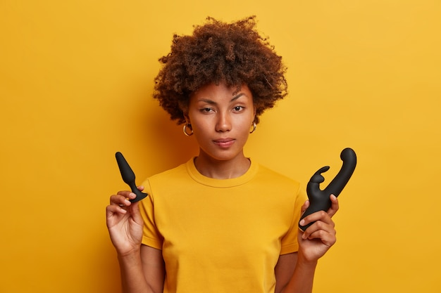 Hesitating african american female holds butt plug to warm up before penetrative play, rabbit shaped vibrator for vagina stimulation, dressed in yellow t shirt. young woman with sex toys indoor