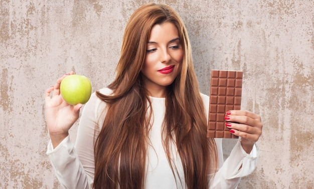 Hesitating woman with apple and chocolate