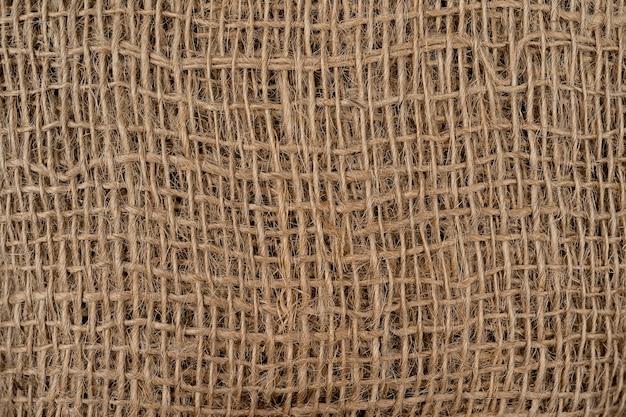 ヘシアン荒布黄麻布織りテクスチャ背景綿織物は斑点でクローズアップ