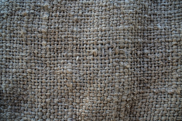The hessian sackcloth woven texture pattern background in light cream yellow beige color