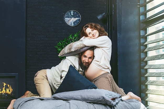 Heterosexual couple beautiful young man and a pregnant woman fighting with pillows on bed in bedroom at home