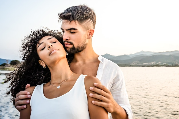 Heterosexual mixed race couple in romance scene at sunset with vintage photo effect filter