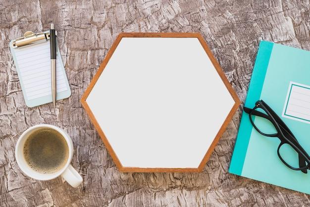 テクスチャの背景にコーヒーと文房具が付いた六角形の白いフレーム