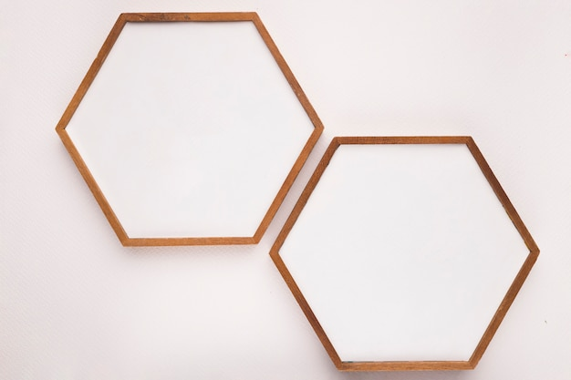 Hexagon wooden frame on white backdrop