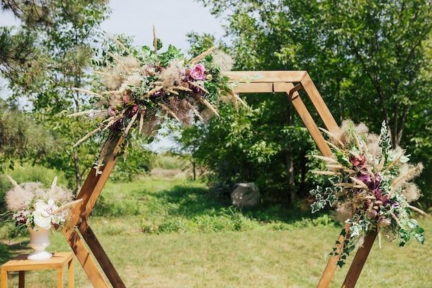 新鮮な緑とバラの六角形の結婚式のアーチ