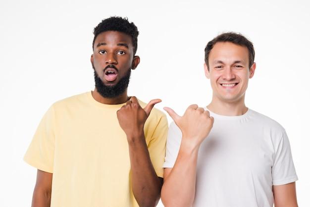 やあ、仲間。白い孤立した壁に立って、人差し指でお互いを指している2人の若いハンサムな男性