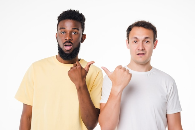 Hey bro. two young handsome men standing on white isolated wall and pointing on each other with index fingers