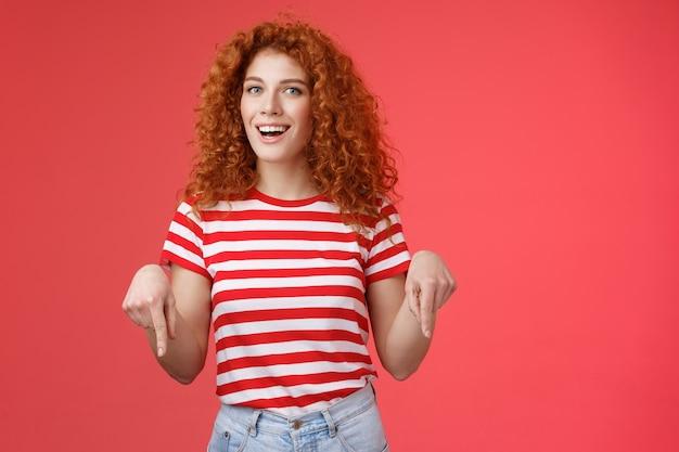 Эй, посмотри, друг. нахальная красивая нахальная рыжая стильная подруга с вьющейся прической носить летнюю футболку, указывая указательным пальцем вниз, улыбаясь, довольна, довольна, подарить потрясающую рекомендацию.