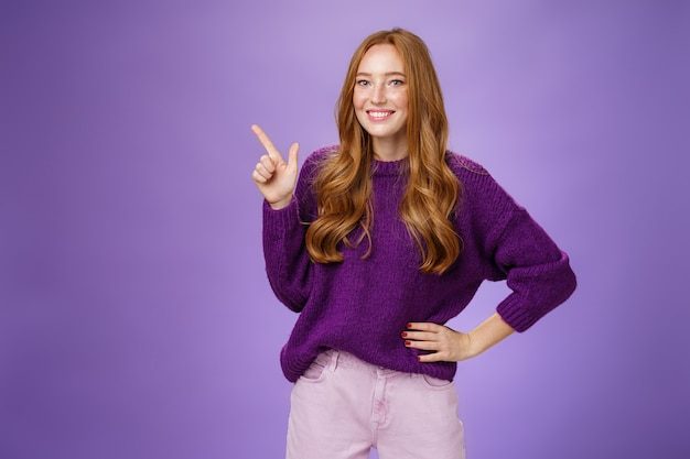 ねえ、ここをクリックしてください。人差し指で左上隅を指して、笑顔で、コピースペースを示して、推薦し、提供する紫色のセーターを着た、フレンドリーに見える魅力的でかわいい赤毛の女性の肖像画。