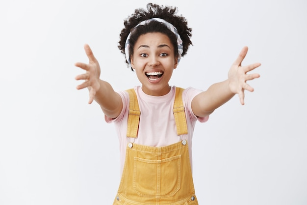 Hey come here and hug me. indoor shot of charming caring friendly-looking dark-skinned woman in headband and overalls pulling hands towards to cuddle best friend, smiling joyfully