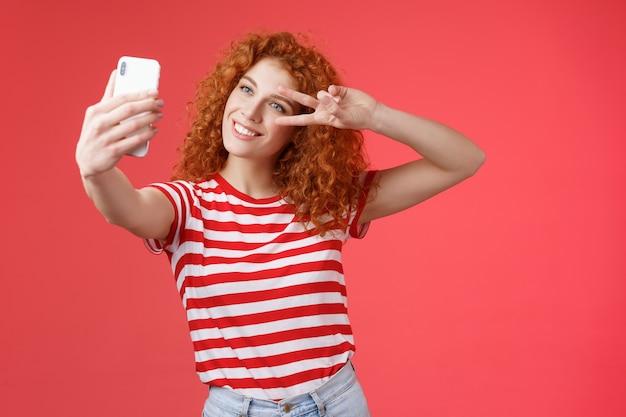 Привет, подписчики, как у вас летние каникулы. веселая самоуверенная стильная модная рыжая кудрявая девушка забастовка позы показывает жест победы мира с экрана смартфона, принимая селфи на красном фоне.