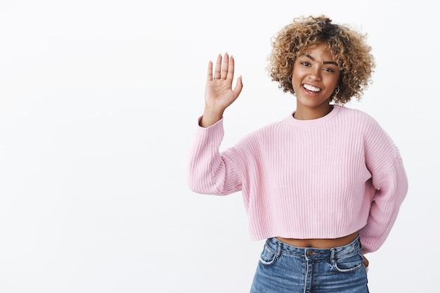하이파이브 주세요. 금발 아프로 헤어스타일을 한 겨울의 세련된 스웨터를 입은 친절하고 즐거운 카리스마 넘치는 여자친구는 손바닥을 들고 친구를 맞이하거나 흰 벽 너머로 카메라를 향해 즐겁고 귀여운 미소를 짓고 있습니다.