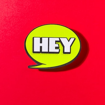 Hey green speech bubble on red background