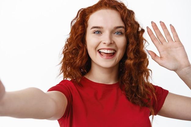 Эй привет. дружелюбная молодая рыжая женщина разговаривает по видео, здоровается и приветствует вас через смартфон, машет рукой, делает селфи, стоит у белой стены