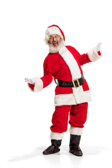 Hey, hello. holly jolly x mas festive noel. full length of funny happy santa in headwear, costume, black belt, white gloves, waves with arm palm standing at studio over white background