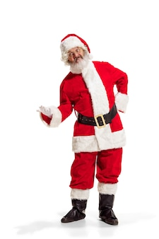 Эй привет. холли веселый х мас праздничный ноэль. полная длина забавного счастливого санта-клауса в головном уборе, костюме, черном поясе, белых перчатках, волнах с ладонью руки, стоящей в студии на белом фоне