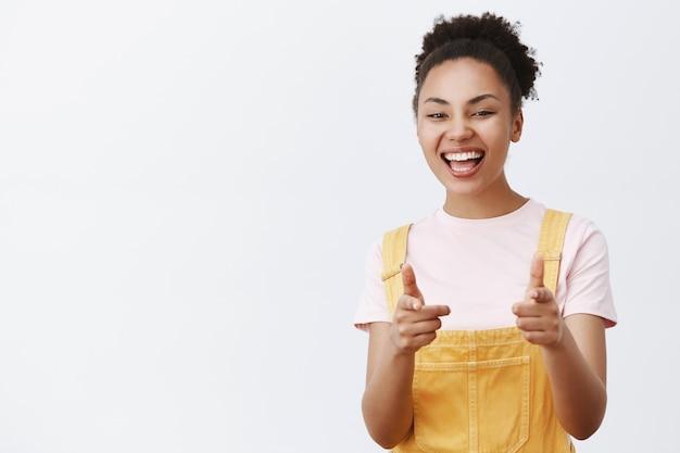 Привет, я тебя знаю. портрет дружелюбной оптимистичной и доброй афроамериканской девочки-подростка в модном желтом комбинезоне, указывающей жестом из пистолета и широко улыбающейся