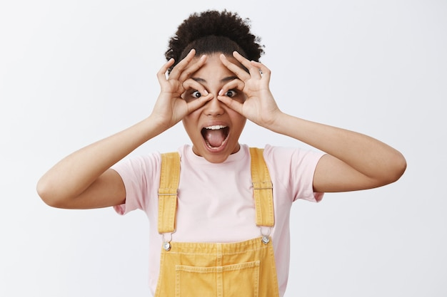 Hey i see you. playful emotive happy girl fooling around in yellow overalls over t-shirt, makign circles with hands and looking through it amazed as if using binoculars or glasses