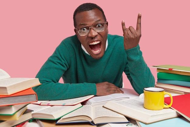이봐, 멋지다! 어두운 피부색의 학생이 로큰롤 제스처를하고 입을 크게 벌리고 큰 소리로 외치며 녹색 스웨터를 입고 책으로 둘러싸여 있습니다.