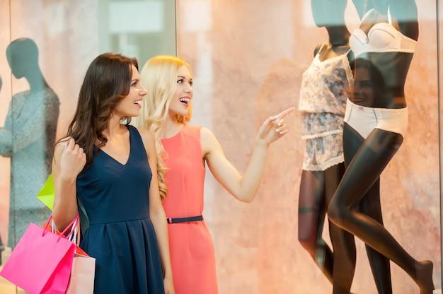 Эй, вы только посмотрите на это! две красивые молодые женщины в платьях держат хозяйственные сумки и указывают в сторону