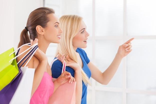 ねえ、それを見てください!ショッピングバッグを持って、離れて指しているドレスを着た2人の美しい若い女性