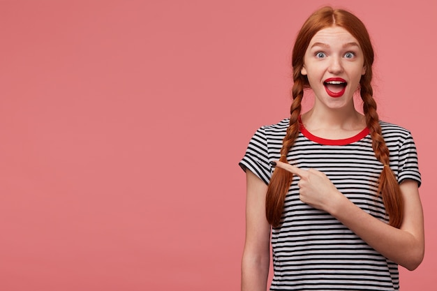Hey, look, it is great! happy inspired red haired teen girl shows with index finger on the empty space on left side,is delighted with the product, advises to pay attention,place for your advertisement