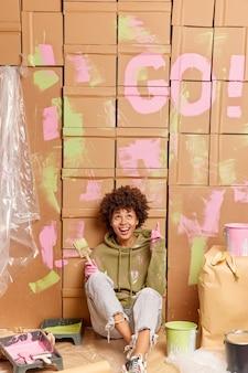 내가 뭘했는지 봐! 밝고 어두운 피부를 가진 민족 여성이 위를 가리키며 집에서 수리하고 방을 재 장식하는 데 바쁜 페인트 도구로 둘러싸인 아파트의 벽을 그리는 방법을 보여줍니다.